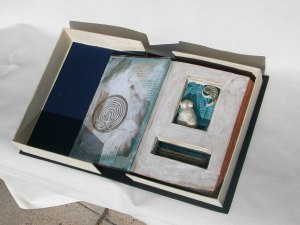 Mixed media assemblage: altered book, hand fabricated clam shell cover, porcelain figure, shell, glass vial.