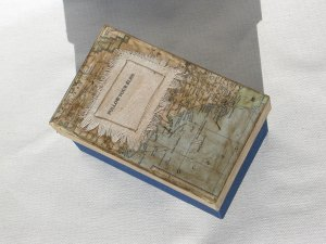 Mixed media assemblage: book board, book cloth, maps, canvas, wire, ceramic poppet, paper, artist's book.