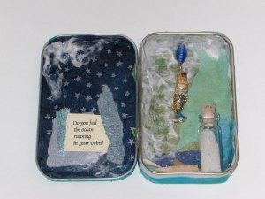 Miniature shrine/assemblage in a mint tin.