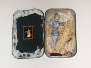 Mixed media assemblage in small tin. Includes ceramic goddess, antique glass cameo, wheat, paper, gems.