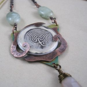 """This mixed media piece was created for a blog hop - """"The Challenge of Music"""" hosted by Erin Prais-Hintz of Tesori Trovati jewelry. It is inspired by a Marillion song of the same name - a favorite of mine since my teen years.You can read about the inspiration and the process on the blog.copper, brass, plastic lens, wool roving, image transfer, chain, gems, Gilders paste."""