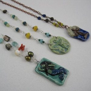 """My """"Mythic Nature"""" line of ceramic pendants are original designs, hand carved in clay. I make plaster molds of the original, streamlining the process and allowing for color variations. They are all handpainted in a mix of glazes and underglazes, front and back, and fired in my kiln.These pendants are paired with semi-precious gems to complete the necklaces."""