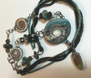 the loosely braided back of the piece - seed beads and leather